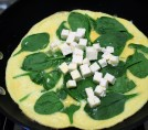 8. Cook until egg is set and spinach wilted. Add cubed Feta in center