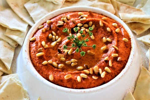 Red Pepper Hummus garnished with toasted pine nuts, olive oil, paprika and a parsley flower